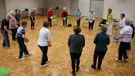 Ein Kreis von Frauen bei der Gesundheits-Gymnastik mit farbigen Ballonen